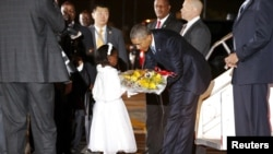 Presiden AS Barack Obama menerima karangan bunga dari seorang gadis cilik saat tiba dengan pesawat Air Force One di bandara internasional Jomo Kenyatta di Nairobi (24/7).