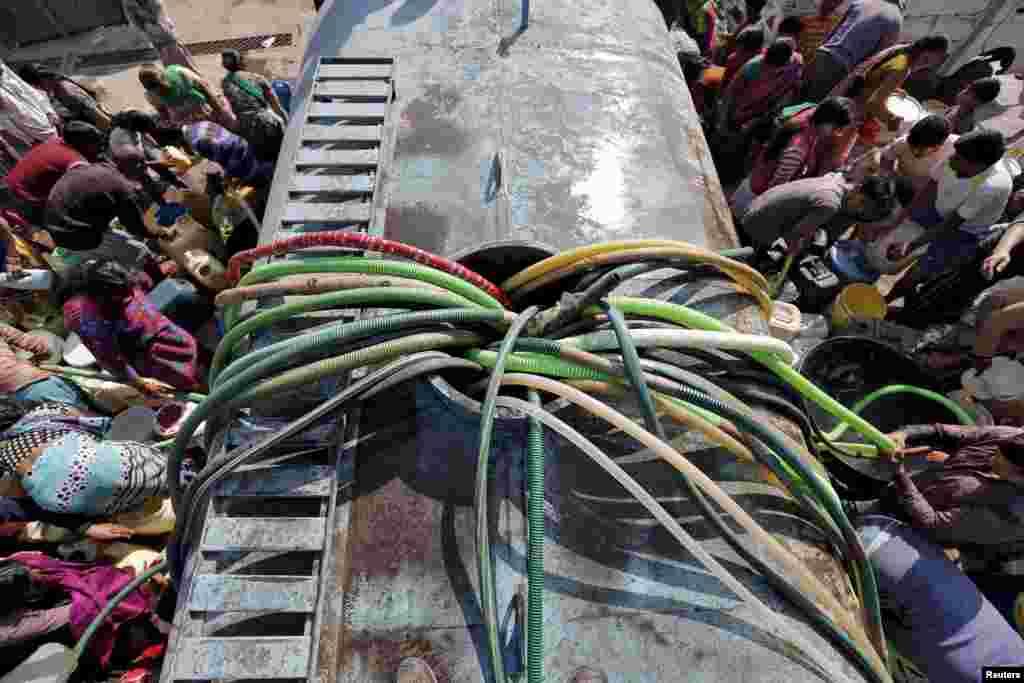 مردم در یک محله فقیر در دهلی هند سعی دارند با شلنگ های شان، از تانکر آب برای بطری های شان جمع کنند.