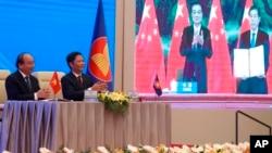 នាយករដ្ឋមន្ត្រីវៀតណាមលោក Nguyen Xuan Phuc (ឆ្វេង) និងរដ្ឋមន្ត្រីពាណិជ្ជកម្មលោក Tran Tuan Anh (ស្ដាំ) ទះដៃនៅជិតផ្ទាំងកញ្ចក់មួយដែលបង្ហាញរូបនាយករដ្ឋមន្ត្រីចិនលោក Li Keqiang និងរដ្ឋមន្ត្រីពាណិជ្ជកម្មលោក Zhong Shan កាន់កិច្ចព្រមព្រៀង RCEP ដ