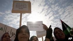 """利比亚妇女3月23日在班加西集会高举英语标语牌,上写""""俄国中国不能代表利比亚人民做决定""""和""""多谢法国"""""""