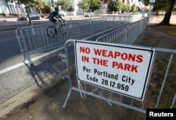 "A ""No Weapons"" sign is seen at a park where the right-wing Patriot Prayer group planned to rally in Portland, Ore., Aug. 4, 2018."