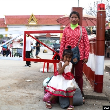 Mother standing near border gate with her six-year-old daughter standing in front of her.