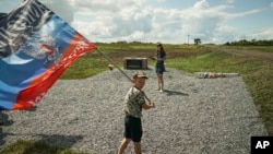 A boy waves a flag of the self-proclaimed Donetsk People's Republic at a memorial to the victims of the Malaysian Airlines MH17 plane crash at the crash site near the village of Hrabove, eastern Ukraine, July 16, 2015.
