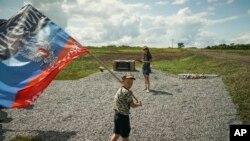 Seorang anak lelaki mengibarkan bendera Republik Rakyat Donetsk, sebuah negara yang diproklamasikan sendiri, di tempat dimana pesawat Malaysian Airlines MH17 ditembak jatuh di desa Hrabove, sebelah timur Ukraina, Kamis, 16 Juli 2015 (foto: AP Photo/Mstyslav Chernov)