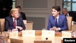 នាយករដ្ឋមន្រ្តីកាណាដា Justin Trudeau (ស្តាំ) និងប្រធានាធិបតីសហរដ្ឋអាមេរិកចូលរួមក្នុងកិច្ចប្រជុំកំពូល G7 នៅទីក្រុង Charlevoix ទីក្រុង Quebec ប្រទេសកាណដា កាលពីថ្ងៃទី០៨ មិថុនា ឆ្នាំ ២០១៨។