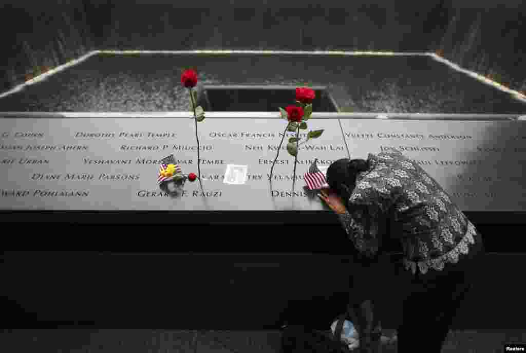 A woman grieves at the site of her husband's inscribed name at the edge of the North Pool during memorial observances on the 13th anniversary of the 9/11 attacks at the site of the World Trade Center in New York, Sept. 11, 2014.