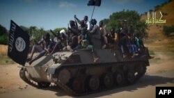 Boko Haram အဖဲြ႔က ထုတ္တဲ့ ဗီြဒီယိုဖိုင္တခုမွာ သံခ်ပ္ကာကားနဲ႔ ဟန္ေရးျပေနတဲ့ စစ္ေသြးႂကြအဖဲြ႔ကို ျမင္ရပံု။