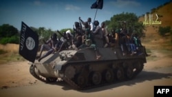 FILE - This image from a Boko Haram video shows its fighters parading in an unidentified town last November. The group has seized the northeast Nigerian town of Chibok, where it had kidnapped 276 schoolgirls in April 2014.