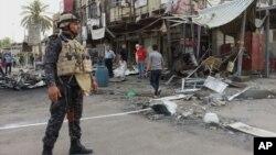 Nhân viên an ninh Iraq đứng gát tại một địa điểm vừa xảy ra vụ đánh bom