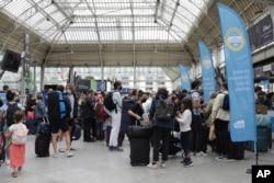 Pemudik mengantre untuk mengakses kereta api saat karyawan kereta api memeriksa kartu kesehatan COVID-19 yang dibutuhkan setiap orang di negara itu untuk masuk kafe, kereta api, dan tempat lainnya, Senin, 9 Agustus 2021. (Foto: AP)