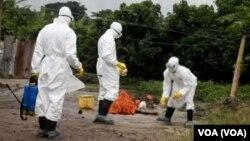 Le personnel de santé s'active à désinfecter les alentours d'une résidence où des personnes infectées d'Ebola habitaient.