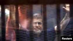 Former Egyptian President Mohamed Mursi waves as he enters for his trial with other Muslim Brotherhood members at a court in the outskirts of Cairo, May 16, 2015.