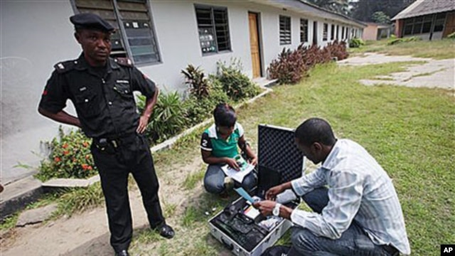 A police officer provides security as Electoral Officials check voter registration material and election equipment at a distribution center in Lagos, Nigeria, 15 Jan, 2011