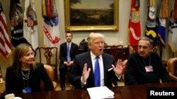 Presiden Amerika Serikat Donald Trump, didampingi CEO General Motors Mary Barra (kiri) dan CEO Fiat Chrysler Sergio Marchionne (kanan), dalam pertemuan dengan CEO industri otomotif AS di Gedung Putih, Washington, 24 Januari 2017. (REUTERS / Kevin Lamarque).