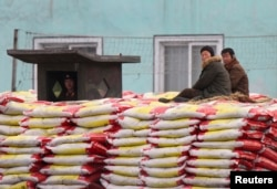 FILE - People sit on sacks of fertilizers as a North Korean soldier stands guard on the banks of Yalu River near the North Korean town of Sinuiju, opposite the Chinese border city of Dandong, Jan. 29, 2014.