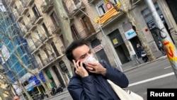 A man wears a protective face mask as he walks along a street, after novel coronavirus has been confirmed in Barcelona, Spain February 25, 2020.
