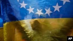 Một người biểu tình chống chính phủ ở Venezuela đứng sau quốc kỳ.