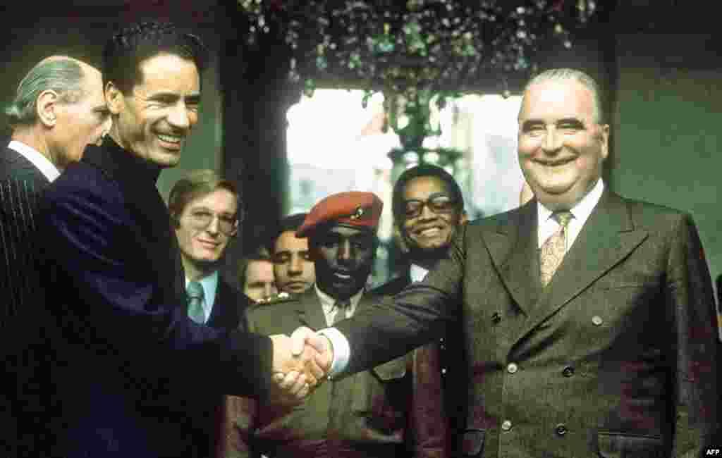 Муаммар Каддафи (слева) обменивается рукопожатием с президентом Франции Жоржем Помпиду 24 ноября 1973 на ступеньках Елисейского дворца в Париже