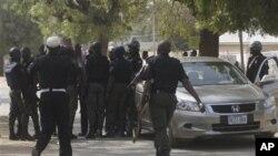 Cảnh sát thẩm vấn 1 người đàn ông không rõ danh tính lái xe đến trụ sở cảnh sát tại Kano, Nigeria, 24/1/2012