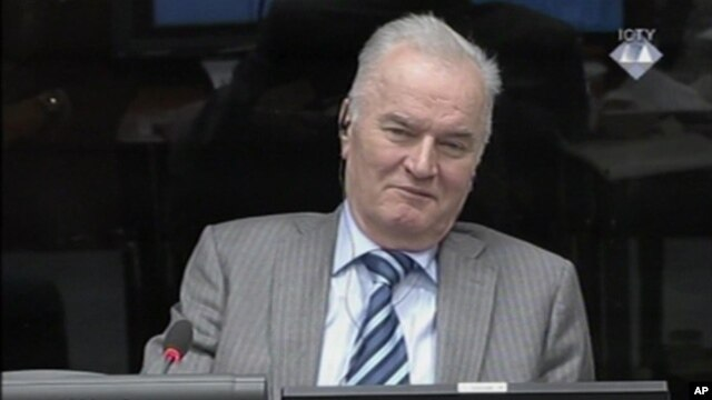 In this image taken from video former Bosnian Serb army commander Gen. Ratko Mladic smiles during his appearance at the Yugoslav war crimes tribunal, Jan. 28, 2014, in the Hague, Netherlands.