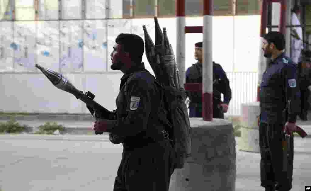 Afghan security personnel stand guard at the site of a deadly attack in Kabul. Officials say the political offices of the president's running mate were hit by a large explosion and stormed by an unknown number of attackers. Nasrat Rahimi, the interior ministry spokesman, said vice-presidential candidate and former intelligence chief Amrullah Saleh survived the attack.