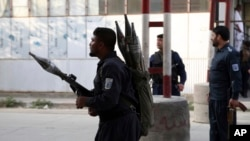 Afghan security personnel stand guard at the site of a deadly attack in Kabul, Afghanistan, Sunday, July 28, 2019.