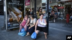 FILE - Elderly women wait at a bus stop in central Athens, Aug. 13, 2015.
