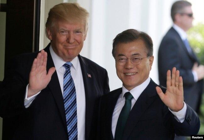 지난해 6월 백악관에서 만난 도널드 트럼프 미국 대통령과 문재인 한국 대통령이 취재진을 향해 손을 흔들고 있다.