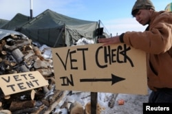 "A man makes a sign that reads ""vet check in"" in Oceti Sakowin camp as ""water protectors"" continue to demonstrate against the Dakota Access pipeline near the Standing Rock Indian Reservation, Cannon Ball, N.D., Dec. 3, 2016."