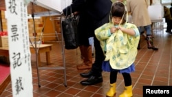 A girl stands next to her father as he fills out his ballot for a national election at a polling station in Tokyo, Oct. 22, 2017. Typhoon Lan is expected to come close to the Japanese capital Monday morning before heading out to sea.