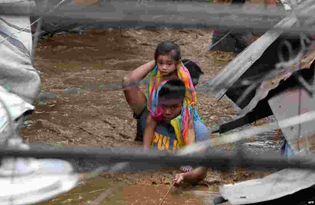 یک پلیس دختر بچه ای را برای رد شدن از خیابان های سیل زده در فیلیپین به دوش می کشد.