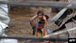 Một nhân viên cảnh sát cõng một bé gái qua một con đường ngập nước ở thành phố Cayagan hôm 22/12/2017, sau khi sông Cagayan tràn bờ vì mưa lớn do bão Tembin mang lại.