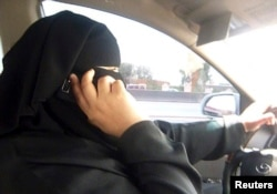 FILE - Umm Ibrahim sits behind the wheel of her vehicle as she drives in Riyadh, an act that is banned in Saudi Arabia.