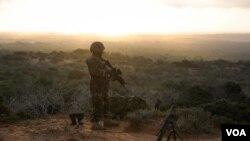 Un soldat, débout, en garde au sommet de la colline au-delà de la ville de Baraawe qui est sous le contrôle d'Al Shabab dans la région du Bas-Shabelle en Somalie, le 5 octobre. AMISOM Photo / Tobin Jones