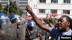 Un policier anti-émeute regarde un manifestant tenant des fleurs dans ses mains pour symboliser la paix à Harare, Zimbabwe, le 17 août 2016.