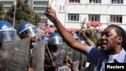 Des manifestants tenant des fleurs dans ses mains pour symboliser la paix, font face à la police anti-émeute à Harare, Zimbabwe, 17 août 2016.