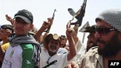 Binh sĩ của phe nổi dậy ăn mừng bên ngoài một căn cứ quân sự gần thị trấn Bani Walid, Libya, ngày 3/9/2011
