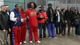 Flamboyant former NBA star Dennis Rodman, fifth from right, poses with three members of the Harlem Globetrotters basketball team, Pyongyang Airport, North Korea, Feb. 26, 2013.