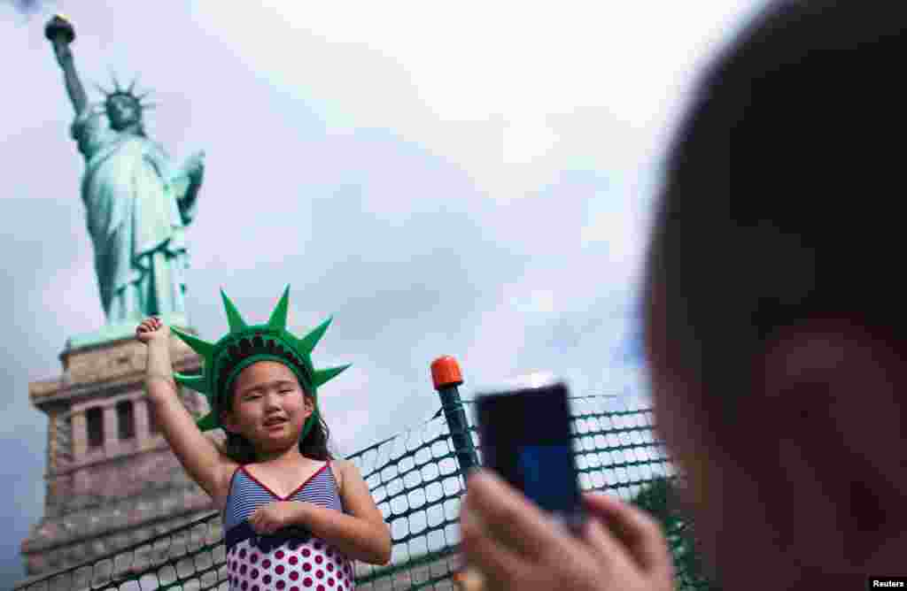 A girl poses as they visit the Statue of Liberty and Liberty Island during its reopening to the public in New York, July 4, 2013. The Statue of Liberty closed in October during Superstorm Sandy.