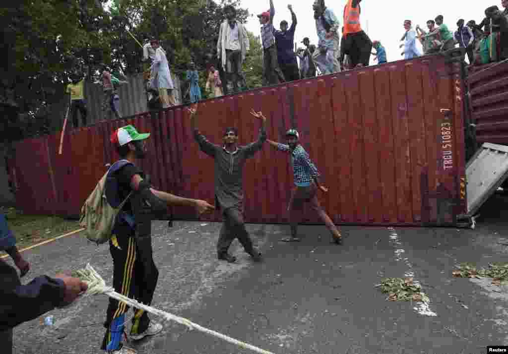 احتجاج کرنے والی جماعتوں کے کارکنوں کنٹینر ہٹاتے ہوئے