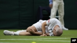 Adrian Mannarino of France lies on the ground in pain during the men's singles first round match against Switzerland's Roger Federer on day two of the Wimbledon Tennis Championships in London, Tuesday June 29, 2021. (AP Photo/Kirsty Wigglesworth)
