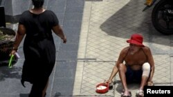 A man begs for money in central Bangkok, Thailand, May 22, 2015. When Thailand's army seized power in a bloodless coup, much of the business establishment quietly cheered them on. A year on, the captains of Thai industry remain firmly behind the junta, despite a lackluster econom