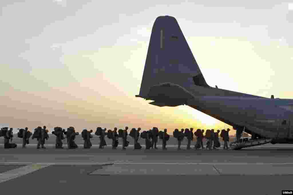 Marines and sailors with Marine Expeditionary Brigade – Afghanistan load onto a KC-130 aircraft on the Camp Bastion flightline, Afghanistan. The Marine Corps ended its mission in Helmand province the day before. (U.S. Marine Corps photo by Staff Sgt. John Jackson)