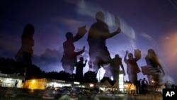 Manifestantes marchan por las calles de Ferguson iluminadas por destellos a la distancia.