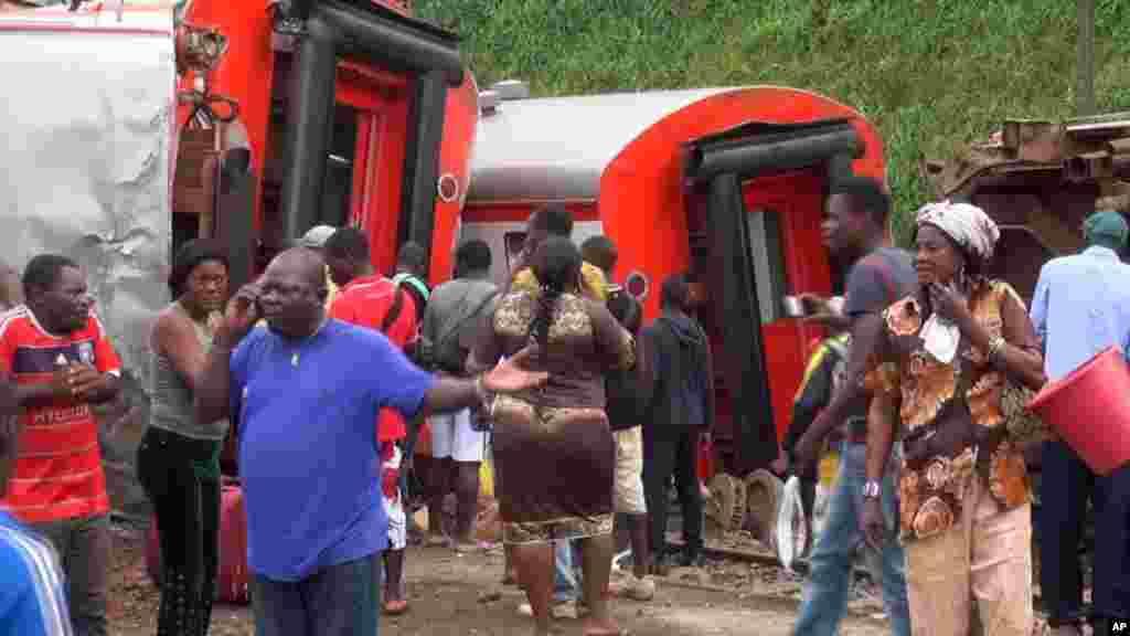 Les rescapés se tiennent à côté des wagons déraillés après l'accident d'un trainà l'entrée de la gare Eseka, au Cameroun, 21 octobre 2016.
