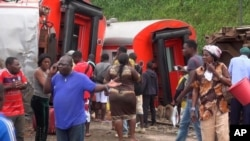 In this image made from video, passengers stand beside derailed train carriages after an accident in Eseka, Cameroon, Oct. 21, 2016.