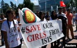 FILE - Women hold a banner during a demonstration marking the first anniversary of Islamic State's surge on Yazidis of the town of Sinjar, in front of the United Nations European headquarters in Geneva, Switzerland, Aug. 3, 2015.