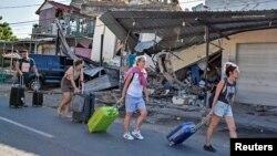 گردشگران خارجی پس از وقوع زمین لرزه از کنار ساختمان های آسیب دیده در لومبوک عبور می کنند.