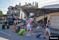 Foreign tourists pull their suitcases as they walk past damaged buildings following a strong earthquake in Pemenang, North Lombok, Indonesia, Aug. 6, 2018.