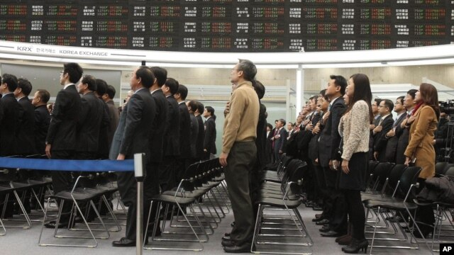 Nhân viên thị trường chứng khoán Hàn Quốc chào cờ trong lễ khai mạc buổi giao dịch đầu tiên của năm 2013 tại Seoul.